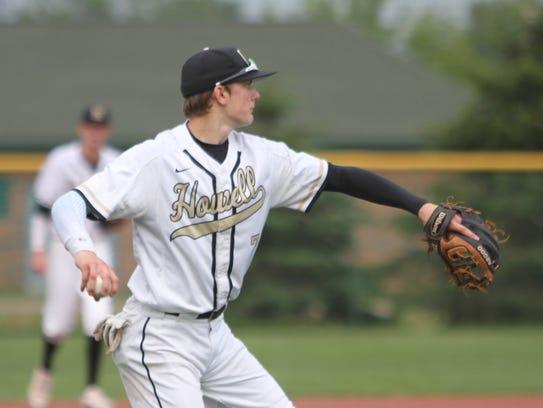 Howell third baseman Evan Mazer throws to first base