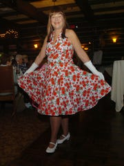 "Sue Surletta wore a 1950s floral dress with a ""fru-fru slip"" and white patent leather shoes as part of the show."