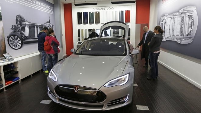 Customers check out a new Tesla all electric car on March 17, 2014, at a Tesla showroom inside the Kenwood Towne Centre in Cincinnati.