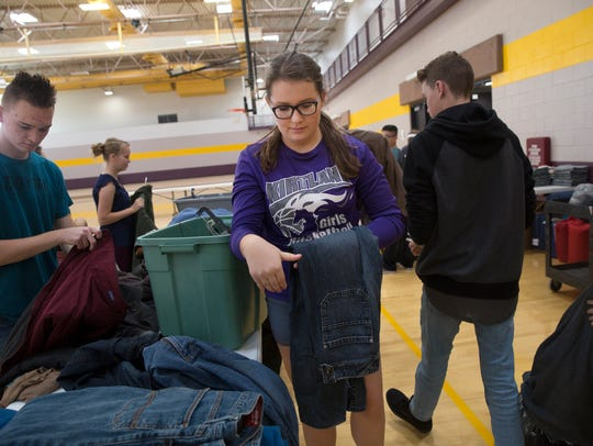 Cody Fordyce, at left, and Brookyn Matthews, center, fold and sort clothing with other members of San Juan College High School student senate Thursday at the Health and Human Performance Center At San Juan College.