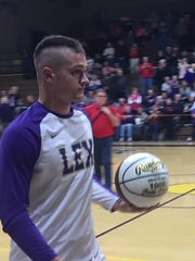 Lexington junior Cade Stover receives a commemorative basketball for joining the 1,000 point fraternity.