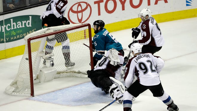 San Jose Sharks' David Schlemko (5) scores the game-winning goal past Colorado Avalanche goalie Spencer Martin, bottom center, during overtime in an NHL hockey game Saturday, Jan. 21, 2017, in San Jose, Calif.