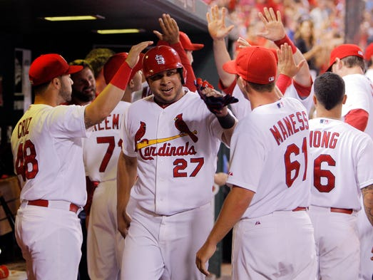 St. Louis Cardinals' Jhonny Peralta is congratulated by teammates after scoring the go ahead run on an RBI single by A.J. Pierzynski during the eighth inning of a baseball game against the Cincinnati Reds, Monday.