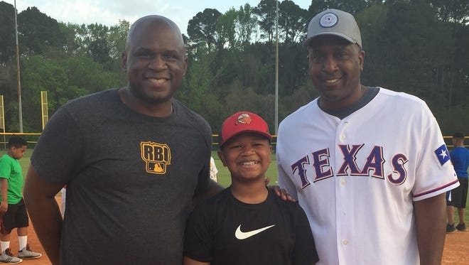 Former Byrd standout Breon Dennis and former Texas Rangers pitcher Darren Oliver pose with Jorden Green during a SPAR clinic Monday at Cargill Park.