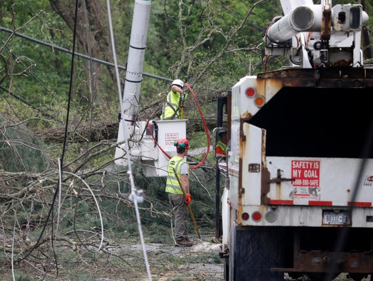 Utility crews work on down trees and power lines on