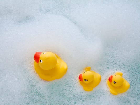 Yellow rubber duckies swimming in bubbles at bath time