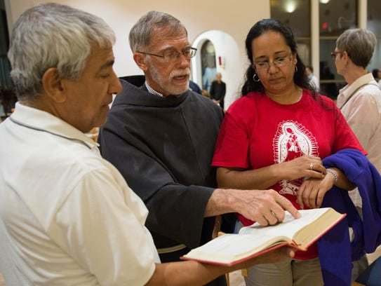 Father Tom Smith, talks with Jorge Taborda and Martha