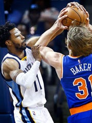 Memphis Grizzlies guard Mike Conley (left) knocks the ball away from New York Knicks guard  Ron Baker (right) during first quarter action at the FedExForum.