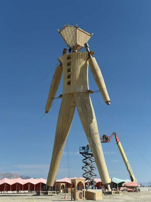 """Artists and volunteers work on the """"Man"""" at the annual Burning Man event on the Black Rock Desert in Gerlach, Nev., on Aug. 24, 2014, a day before the event opens to ticket holders."""