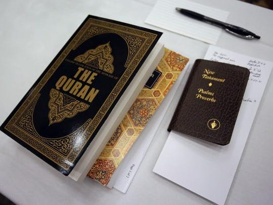 The Quran and a book containing some books of the Bible sit on a table during a meal break at the presentation on Islam at the Holiday Inn in Marshfield, Saturday, May 2, 2015. The central Wisconsin Moslem community is thinking about locating a Mosque in Wausau.