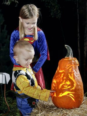Luke Crownover, 2, of West Milwaukee, and his sister, Becca, 8, check out a spooky jack-o-lantern at Boo at the Zoo.