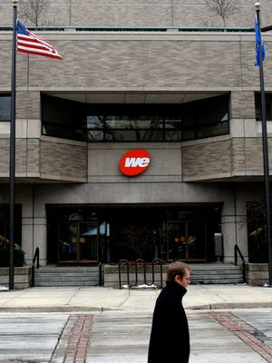 A man walks past the WE Energies building in Milwaukee.