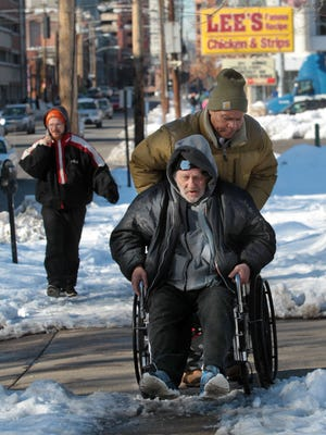 Charles Hickman pushes James Kemmerling's wheelchair over a spot of ice on the sidewalk in front of the Northern Kentucky Emergency Cold Shelter in Covington, where both men are staying during cold weather.