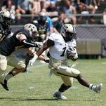 D.J. Knox of the Gold team is chased by Danny Ezechukwu and Race Johnson of the Black team in the first half during Purdue's spring football game Saturday, April 16, 2016, at Ross-Ade Stadium. Knox collapsed onto the turf at the end of the run with an apparent knee injury. He left the game and did not return. The Black team defeated the Gold 23-17.