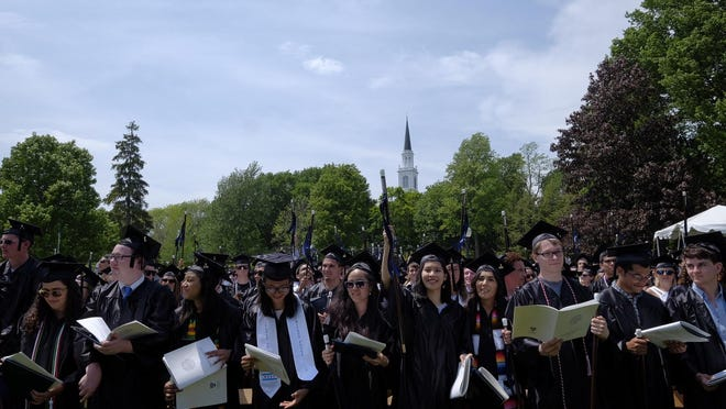 Middlebury graduates wave their canes in the air during the college's commencement ceremony on Sunday. After getting their diplomas, they each received a cane, which is a replica of the cane left to the college by one of its founders, Gamaliel Painter. The original hangs in the president's office. The replica canes were made by Hinesburg craftsman John Lomas.