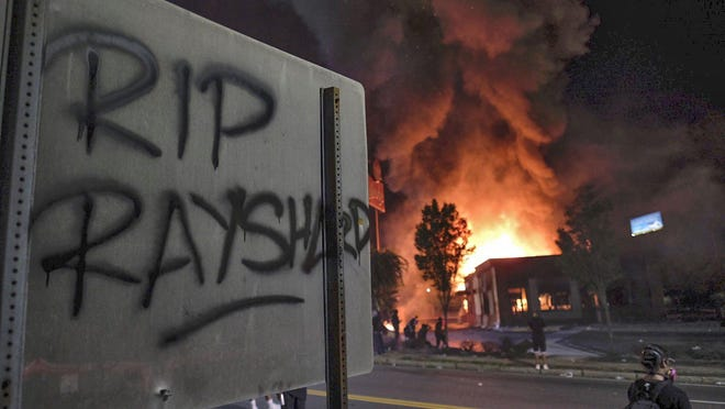A Wendy's restaurant, background, burns Saturday night, June 13, 2020, in Atlanta after demonstrators set it on fire. Demonstrators were protesting the death of Rayshard Brooks, a black man who was shot and killed by Atlanta police Friday evening following a struggle in the Wendy's drive-thru line.
