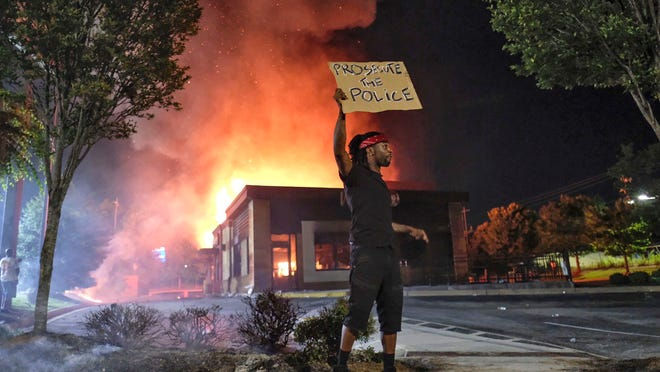 A protester holds a sign as a Wendy's restaurant burns Saturday in Atlanta after demonstrators allegedly set it on fire. Demonstrators were protesting the death of Rayshard Brooks, a black man who was shot and killed by Atlanta police Friday evening following a struggle in the Wendy's drive-thru.