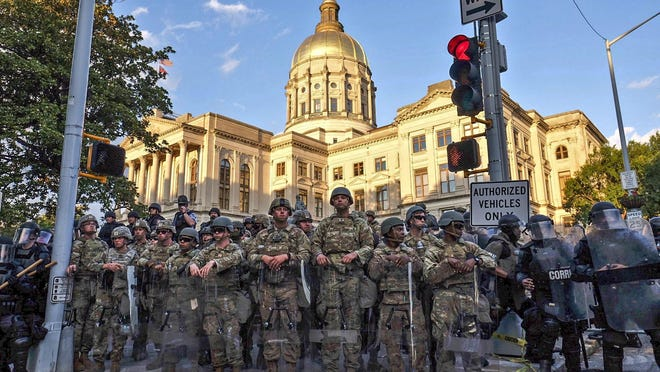 Authorities stand guard around the Georgia state Capitol as protests continued in Atlanta on Sunday, May 31, 2020.