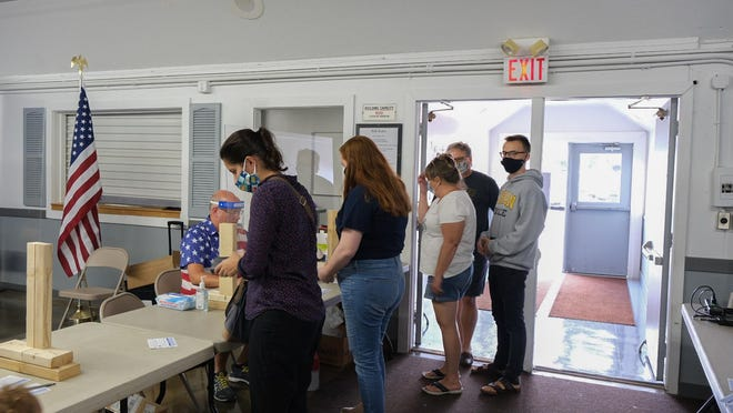 Voters line up to sign in Tuesday at the Adrian polling location at the Lenawee County Fair & Event Grounds during the Michigan primary election.