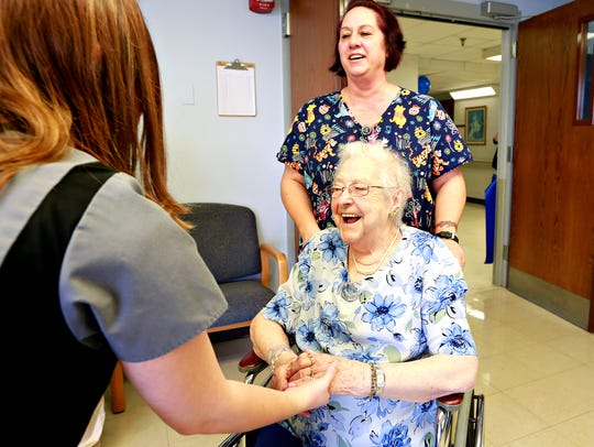 From left, physical therapist Erin Schaller greets