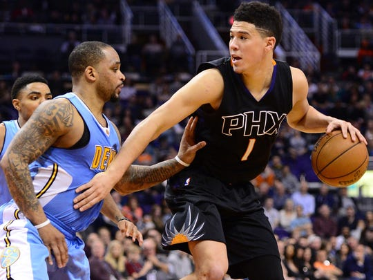 Phoenix Suns guard Devin Booker (1) handles the ball against the Denver Nuggets at Talking Stick Resort Arena.