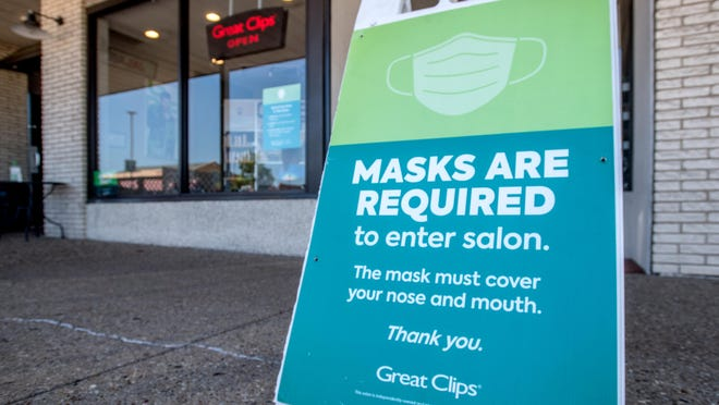 A sandwich board on the sidewalk urges customers to wear face masks at the Great Clips barbershop at the Metro Centre in Peoria.