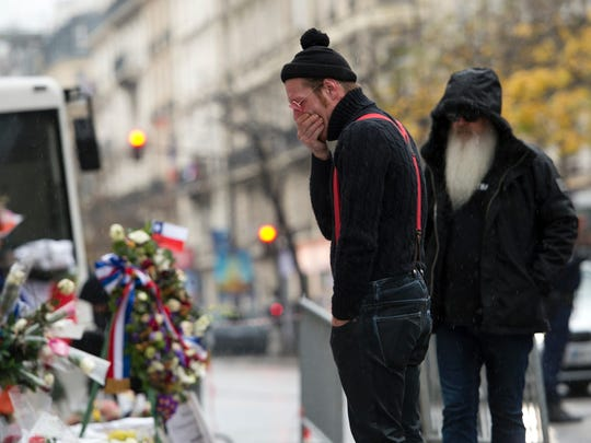 Eagles of Death Metal band members Jesse Hughes (L) and Dave Catching pay tribute to the victims of the November 13 Paris terrorist attacks at a makeshift memorial in front of the Bataclan concert hall on Dec. 8, 2015 in Paris.