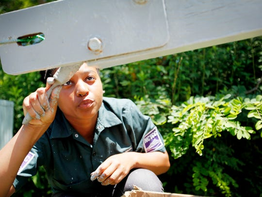 Jessica Johnson, 16, of Raleigh, paints a gate at Mount