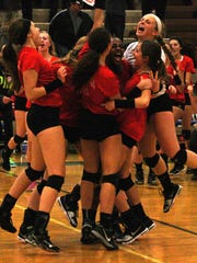 Livonia Churchill volleyball players celebrate seconds after winning a Class A district championship Friday night.