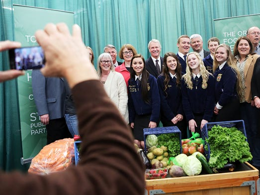 After the signing, Gov. John Kitzhaber poses with members of the Perrydale and Sheridan chapters of Future Farmers of America. Gov. Kitzhaber signed a bill into law at the Oregon Food Bank that will give farmers and other food producers a 15 percent tax credit on the wholesale price of their donations to food banks and other food networks.