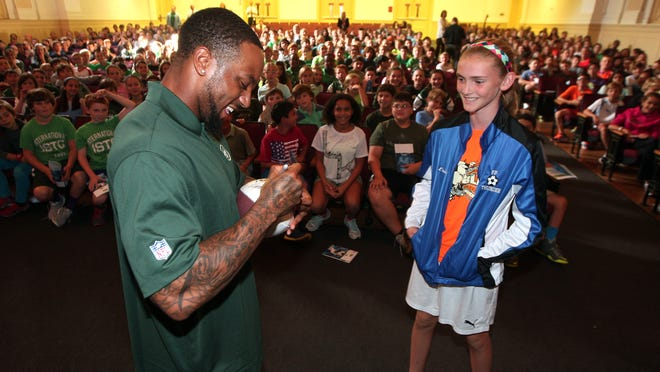 Jets cornerback Kyle Wilson signs a football for 6th grader Erin Martin of the Ridgedale Middle School. Wilson challenged the students to exercise during the kickoff of the Jets Play 60 Challenge at Madison Junior High School.