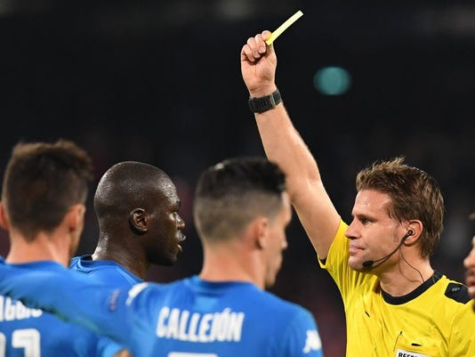 Referee Felix Brych shows the yellow card to Napoli's Kalidou Koulibaly during the Champions League Group F soccer match between Napoli and Manchester City, at the San Paolo stadium in Naples, Italy, Wednesday, Nov. 1, 2017. (Ciro Fusco/ANSA via AP)