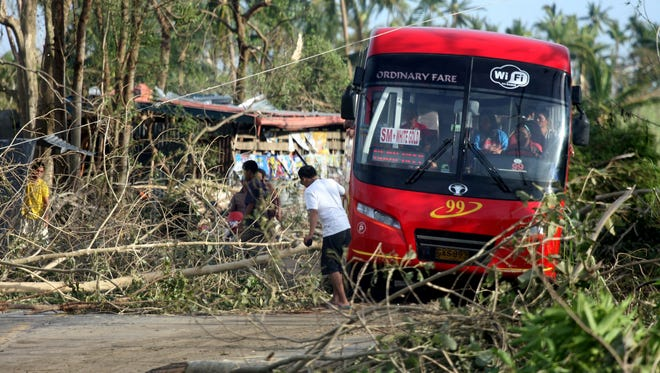 People remove fallen trees from a road in Daanbantayan town, north Cebu, central Philippines on Nov. 10, 2013.