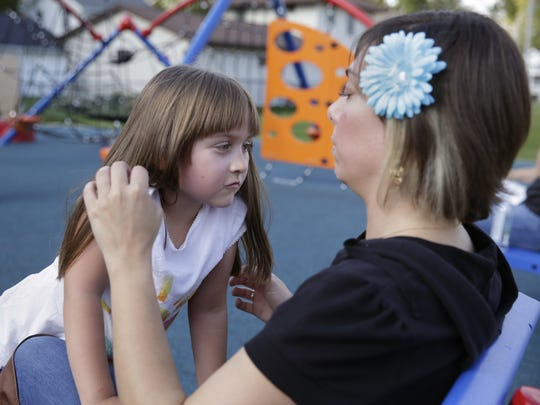 Emily De Young jumps into her mother Kate De Young's lap while at the playground outside St. Margaret Mary Elementary School Monday, Sept. 28, 2015, in Neenah, Wis. Danny Damiani/Post-Crescent Media