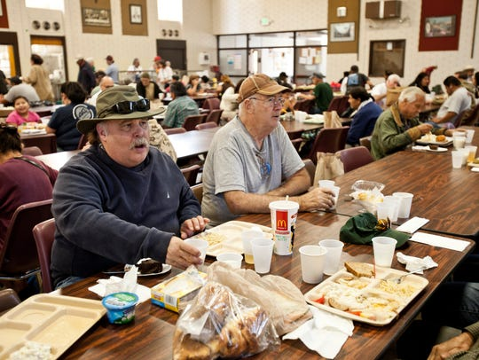 Mark Alward, left, and Larry McDowell eat lunch at