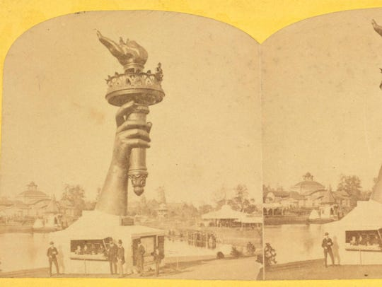 A stereo postcard shows the arm raising the light of