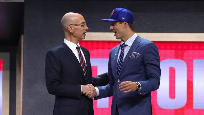 Luke Kennard walks on stage with NBA commissioner Adam Silver after being drafted 12th overall by the Detroit Pistons during the first round of the 2017 NBA draft at Barclays Center on June 22, 2017.