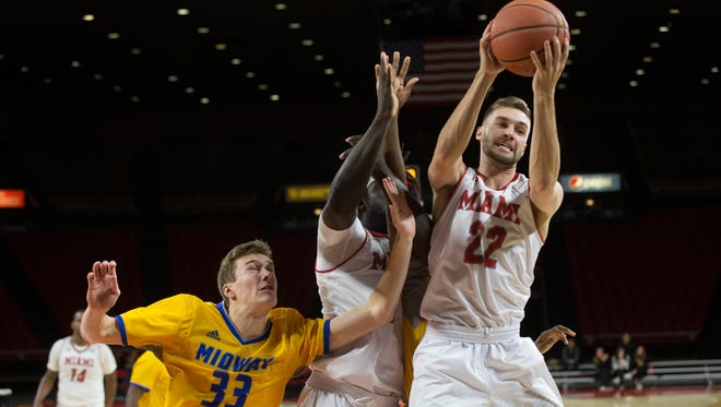 Moeller graduate Grant Pitman grabs a rebound in the Miami University game with Midway. He scored seven points and had four rebounds in his four minutes of play.