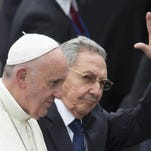 President Raul Castro waves as he escorts Pope Francis during the pope's arrival ceremony at the airport in Havana in 2015.