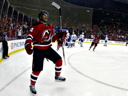 Devils center Adam Henrique reacts after scoring a
