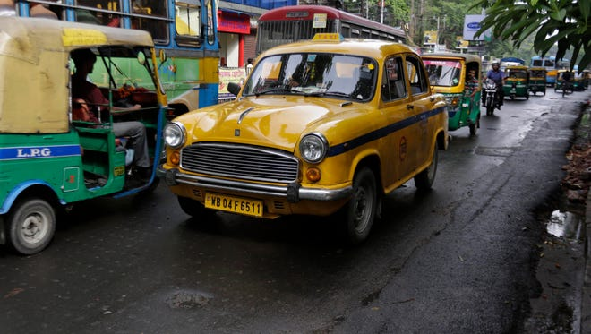 An Ambassador taxi rolls past other vehicles through a busy road in Calcutta.