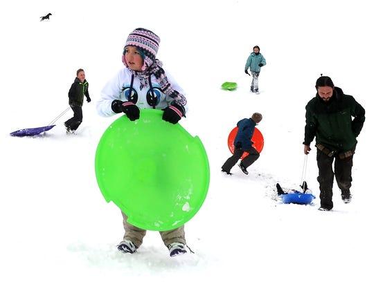 People enjoy sledding in Plumas Park on a snowy Thursday