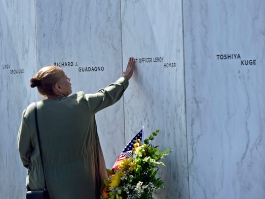 An unidentified woman touches the  Wall of Names in