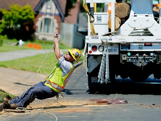 Keegan Parker pulls a line while a crew from Davis H. Elliot Co. from Lexington, Kentucky, works to repair damaged utility poles along Vollintine near McLean on May 30, 2017.