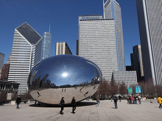 """People walk past the Cloud Gate sculpture, aka """"The Bean,"""" at the north end of Millennium Park in Chicago, Ill."""