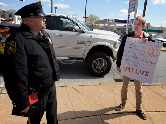Northern Regional Police Officer Mark Allen checks on sole gun rights protestor and Dover Area High School junior Ethan Snyder who chose to take part in the 4/20 walkout of school and position himself at the Dover square Friday, April 20, 2018. Snyder says he is prepared to face a one day in-school suspension for the action. Bill Kalina photo
