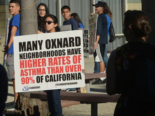 Protesters are seen in this file photo carrying signs outside the Oxnard Performing Arts & Convention Center in opposition to the Puente Power Project that NRG Energy Inc. wanted to build at Mandalay State Beach in Oxnard. The proposal was scrapped and a 100-megawatt battery storage project is poised to be the replacement.