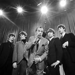 """Variety TV-show host Ed Sullivan (center) stands with The Beatles during a rehearsal Feb. 9, 1964, for the British group's first American appearance on the """"Ed Sullivan Show"""" in New York. on Feb. 9, 1964. From left: Ringo Starr, George Harrison, Sullivan, John Lennon and Paul McCartney. The rock 'n' roll band known as """"The Fab Four"""" was seen by 70 million viewers."""