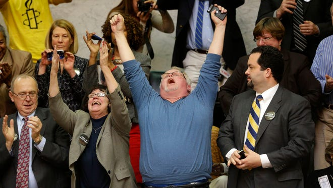 Kirk Bloodsworth, center,  the first American sentenced to death row who was exonerated by DNA, reacts after watching the Maryland General Assembly approve a measure to ban capital punishment in March of 2013.