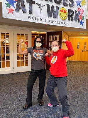 Evelyn Oquendo, director of dining services at Holden Rehab, and Abbi Wood, registered dietitian, show off their hero poses.